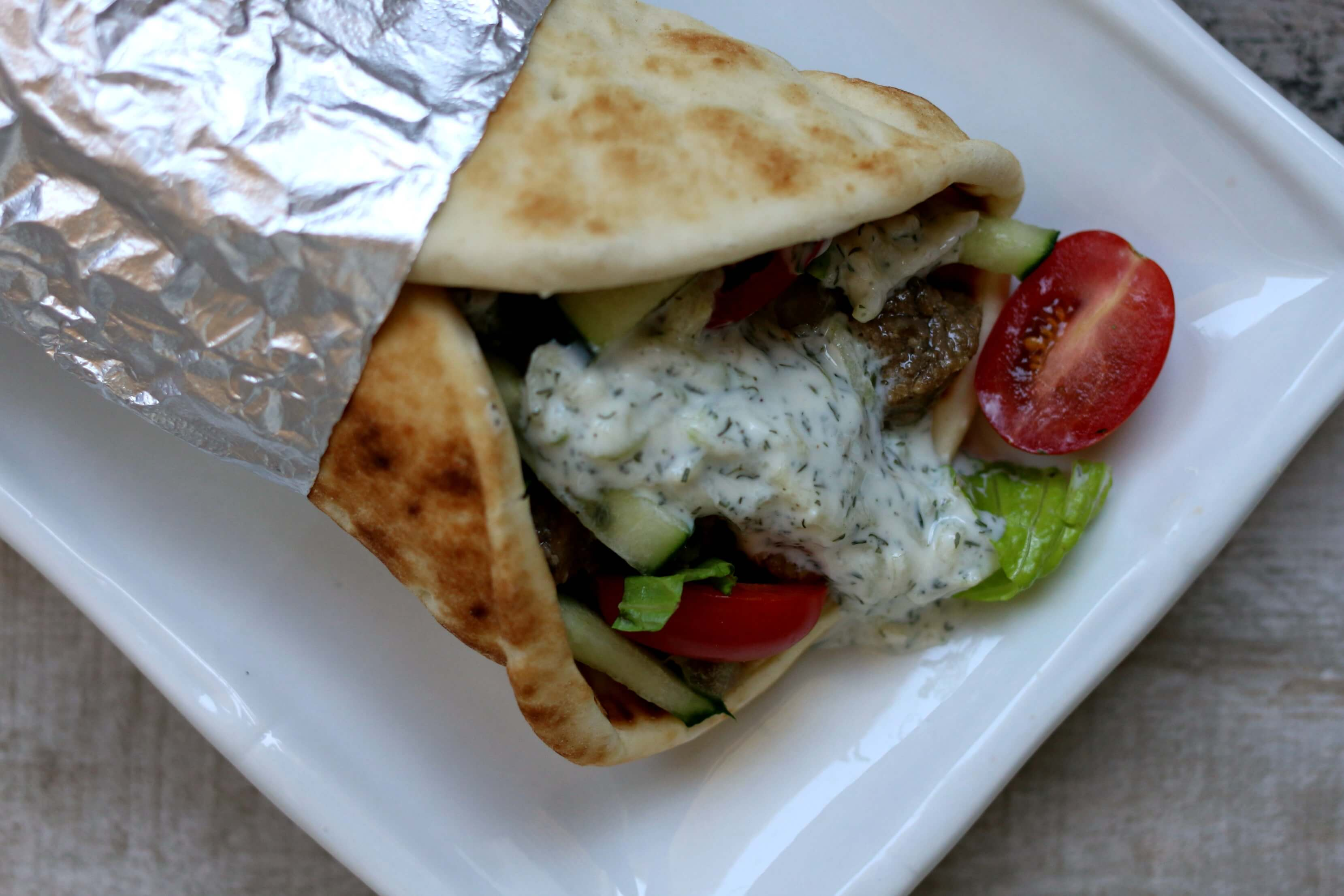 Slow Cooker Beef Gyros Recipe: Tender pieces of beef with soft onions, juicy tomatoes, crisp lettuce, creamy cucumber yogurt sauce all wrapped up in soft, melt in your mouth pita bread. And the best part of this recipe is that the beef is made in the slow cooker freeing up your time and making your kitchen smell good all day long.