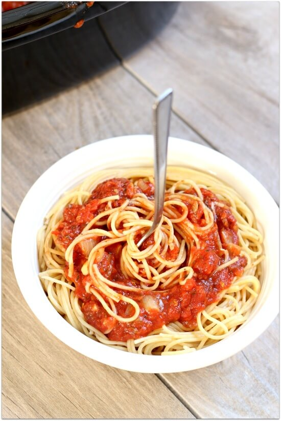 Don't buy cans or jars spaghetti sauce at the grocery store...make it at home! Make it at home in your slow cooker. It's super easy and tastes amazing after simmering all day long. Make a huge batch and freeze the leftovers for an easy dinner another night.