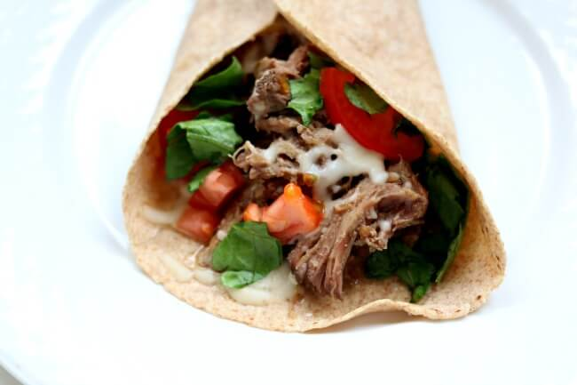 Slow Cooker French Dip Tacos--tender, moist shredded roast beef rolled up in a soft flour tortilla and topped with melty mozzarella cheese. Dip it in au jus sauce for best results!