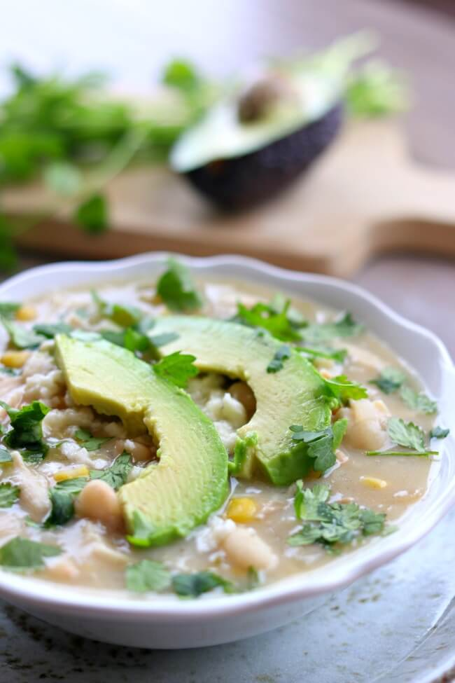 Slow Cooker Healthy White Turkey Chili--a creamy dried white bean chili with tender bites of turkey, creamy broth made with protein-packed Greek yogurt, crumbly queso fresco, slices of avocado and a splash of lime juice for flavor.