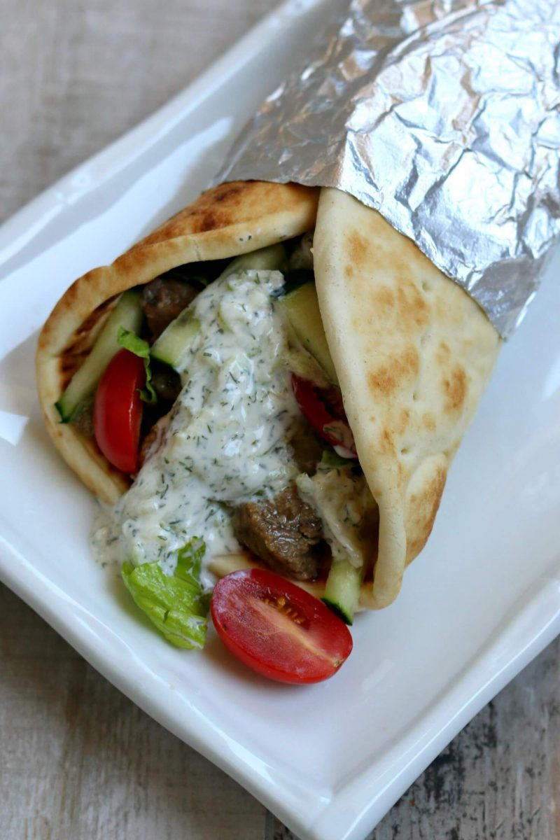 Instant Pot Beef Gyros--Tender pieces of beef with soft onions, juicy tomatoes, crisp lettuce, creamy cucumber yogurt sauce all wrapped up in soft, melt in your mouth pita bread. The beef is cooked until tender in your electric pressure cooker in less than an hour.
