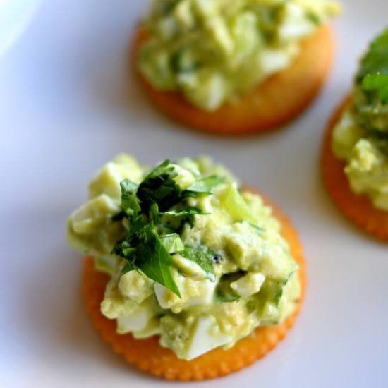 Avocado Egg Salad RITZ Cracker Snacks—smashed avocado is mixed with hard boiled eggs, chopped tomatillos, creamy Greek yogurt and cilantro and then slathered on top of a RITZ Cracker for a perfect snack or appetizer.