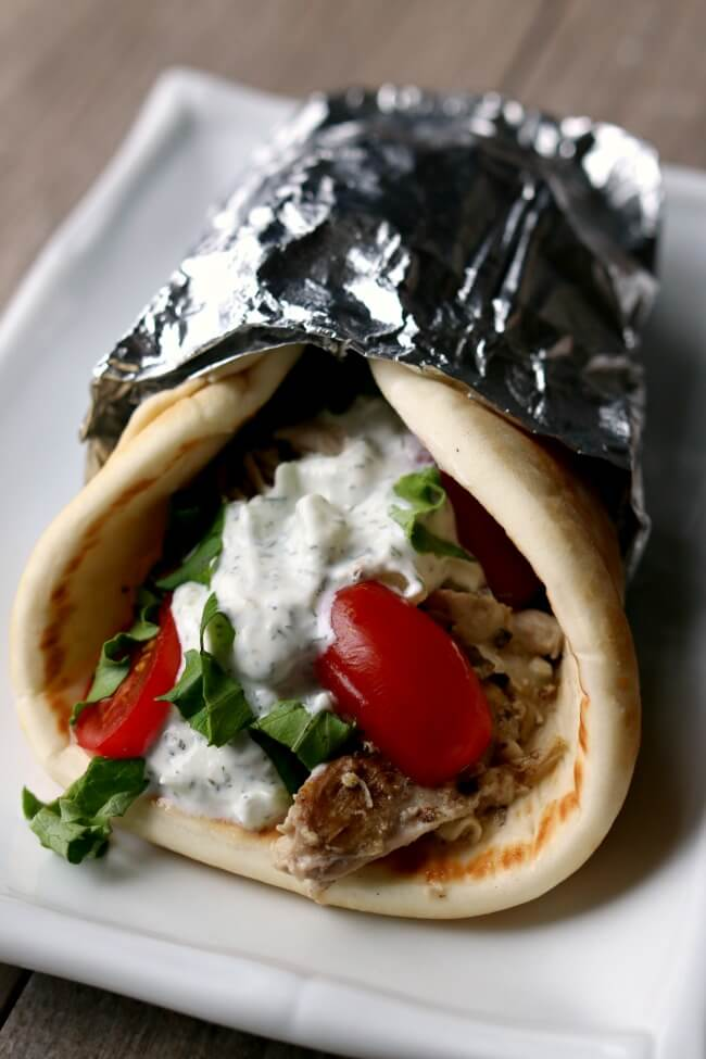 Instant Pot Chicken Gyros--tender, juicy seasoned chicken and onions piled onto soft pita bread and topped with a creamy cucumber yogurt sauce, tomatoes and lettuce. A perfect meal for any night of the week.