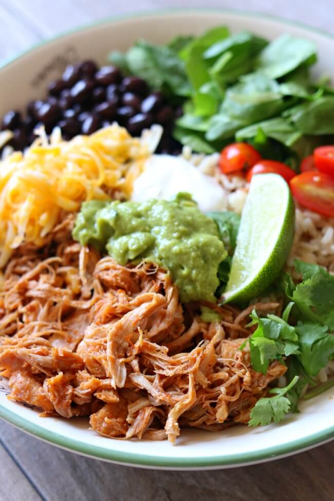 Instant Pot Burrito Bowls--perfectly tender and shreddable 5 ingredient pork is cooked quickly in your Instant Pot and then served with rice, guacamole, black beans, sour cream and more of your favorite toppings.