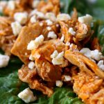 Slow Cooker Buffalo Chicken Lettuce Wraps--shredded chicken coated with buffalo sauce and topped with blue cheese crumbles is wrapped up in crisp lettuce leaves. You can make these flavorful lettuce wraps with just 4 ingredients!