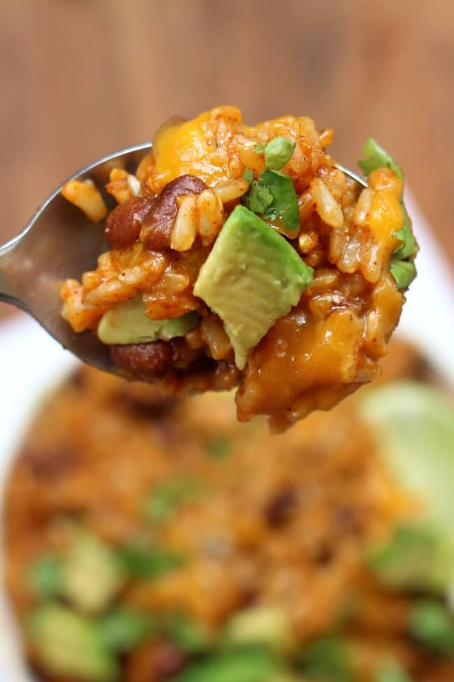 Instant Pot Cheesy Enchilada Rice--brown rice is pressure cooked with enchilada sauce and spices in minutes and then topped with sharp cheddar, diced avocado and a wedge of lime.
