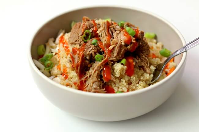 Instant Pot Pork Quinoa Cabbage Bowls--pork is cooked until fork tender with chili garlic sauce and a secret ingredient. The meat is added to a bowl with shredded cabbage, quinoa, diced green onions and finally topped with a drizzle of sriracha. This makes a beautiful and delicious summer meal.