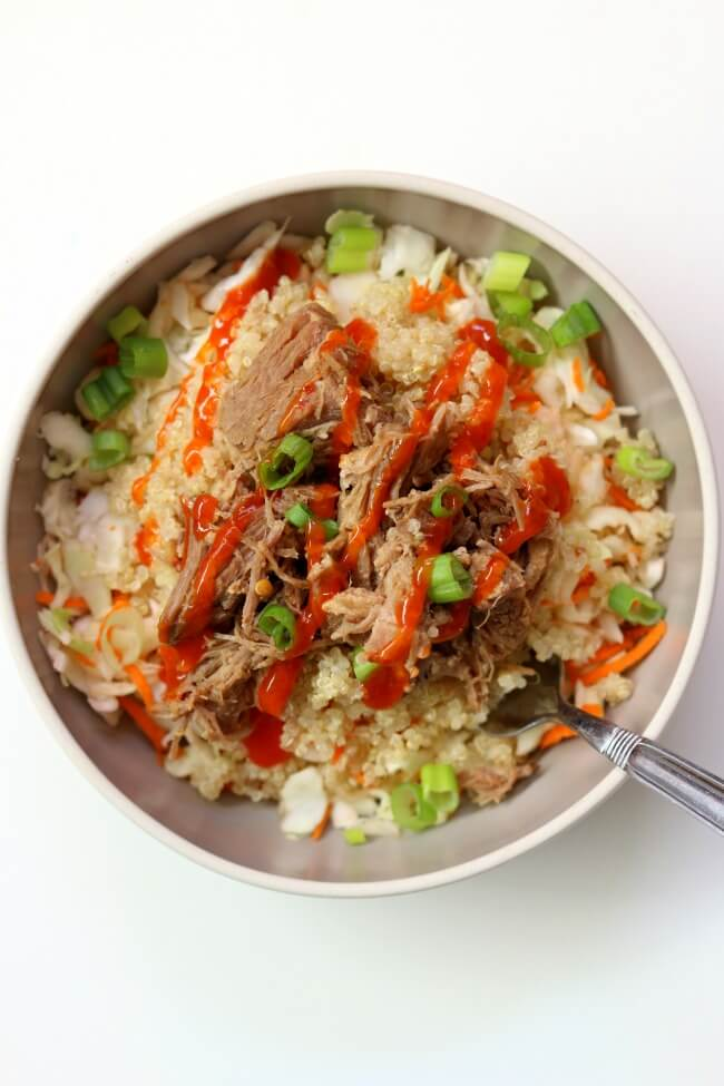 Slow Cooker Pork Quinoa Cabbage Bowls--pork is cooked until fork tender with chili garlic sauce and a secret ingredient. The meat is added to a bowl with shredded cabbage, quinoa, diced green onions and finally topped with a drizzle of sriracha. This makes a beautiful and delicious summer meal.