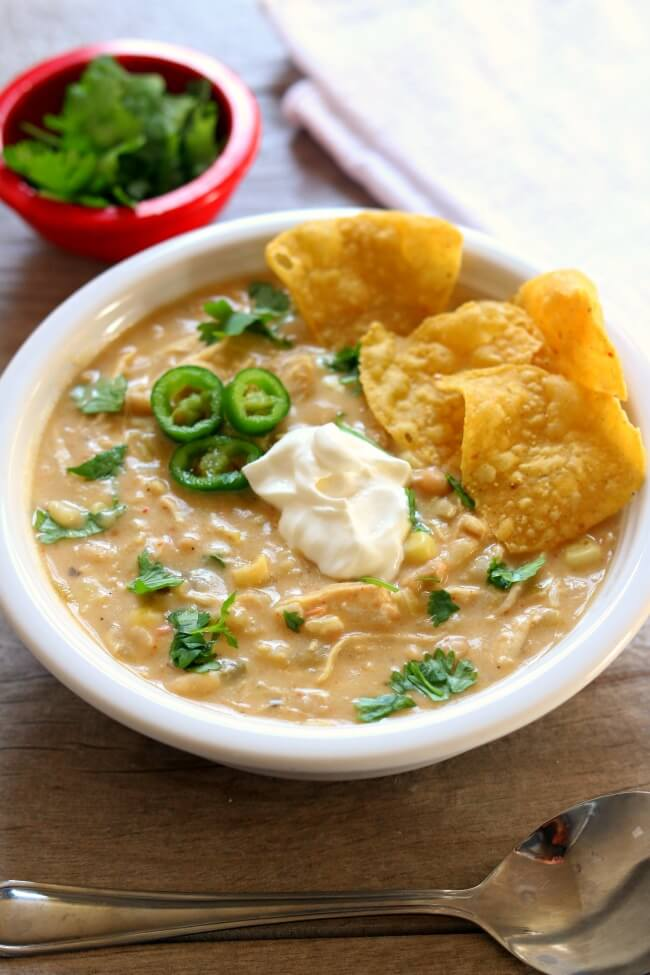 Instant Pot Green Chili Chicken Enchilada Soup--thick and creamy soup with all the flavors from salsa verde chicken enchiladas. Chicken and rice cook quickly in your pressure cooker along with enchilada sauce, green chilies, white beans and flavorful spices. Cream cheese and sweet corn are stirred in at the end along with fresh lime juice for a splash of flavor.