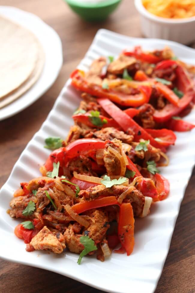 Instant Pot/Slow Cooker Pork Chop Fajitas--make amazingly flavorful fajitas (thanks to a secret ingredient) in the Instant Pot or slow cooker with pork chops. When you buy those inexpensive mega packs of pork chops use this recipe to mix up dinner and bring something new to the table (literally).