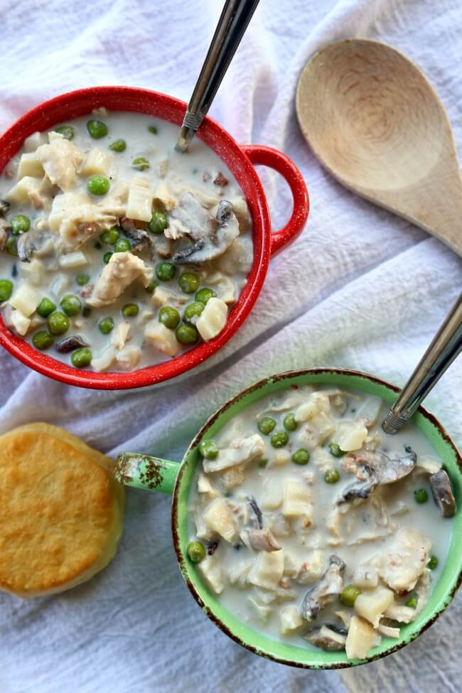 Slow Cooker Chicken Pot Pie Soup--all the flavors from chicken pot pie in a soup! This super easy recipe is made in in your slow cooker. It can be made with raw chicken or leftover cooked turkey or chicken. Serve the soup topped with a biscuit to make it feel like the crust of a pot pie.