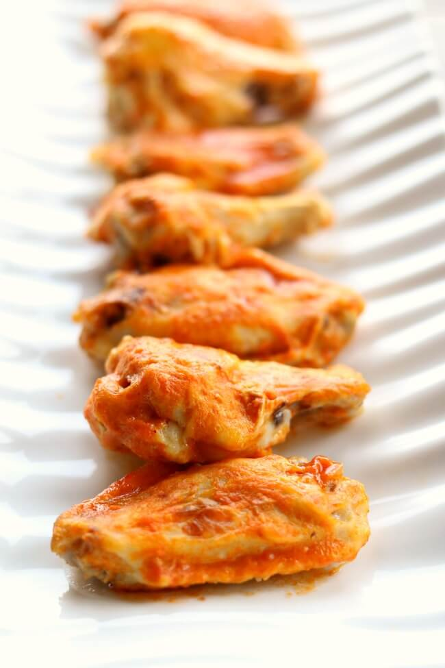 Instant Pot Buffalo Wings--throw a bag of frozen chicken wings in your electric pressure cooker and cook for just 4 minutes, baste with delicious buffalo wing sauce and broil in your oven for another 4 minutes and you have super tender and flavorful wings.