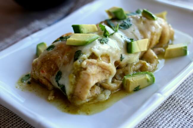 Instant Pot Smothered Green Sauce Enchiladas--homemade Cafe Rio style mild tomatillo sauce is simmered in your electric pressure cooker along with chicken breasts to create the base of your enchiladas. The meal is finished off in the oven when shredded chicken, green sauce and monterey jack cheese are wrapped in flour or corn tortillas and baked. Top each enchilada with avocado slices and a bit of sour cream and you have a party in your mouth.
