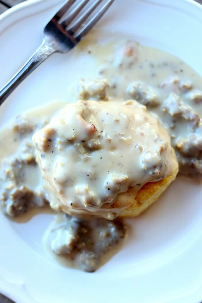 Instant Pot Sausage Gravy--country style gravy made with ground sausage and diced bacon is infused with flavors as it is quickly pressure cooked. When served over freshly baked biscuits (homemade or from a can) it tastes like a good old fashioned southern breakfast (although we eat this often for dinner).