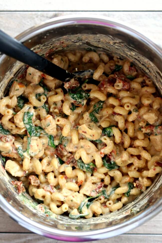 Instant Pot Tuscan Chicken Pasta--curly pasta is enveloped in a creamy parmesan, basil and cream cheese sauce with bites of sun-dried tomatoes, spinach and tender chunks of chicken.