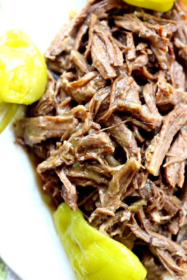 Slow Cooker Mississippi Roast (no packets)--with just a handful of ingredients and your trusty crockpot you can make the best roast of your life. This particular recipe has no packets of ranch or au jus like the original recipe calls for.  The meat is slightly spicy and infused with flavor. This roast is perfect served with mashed potatoes or on a crusty roll as a sandwich.