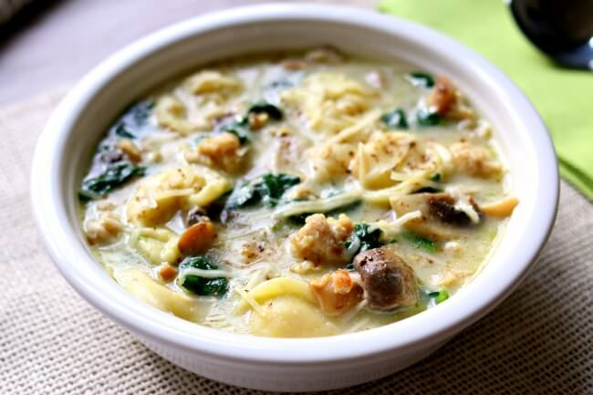 "Slow Cooker Tortellini Soup with Parmesan, Chicken Sausage and Mushrooms needs to make its place on your menu this week. My husband said ""this is maybe the best soup I've ever had!"" It's slightly creamy (but doesn't go overboard with dairy) and has amazing flavor thanks to the chicken sausage. It also has a nice pop of color from the chopped spinach."