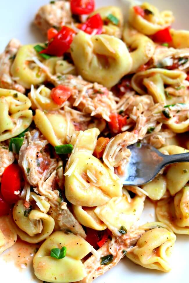 Instant Pot Creamy Basil Chicken and Tortellini--tender bites of chicken breast and cheesy tortellini are served in a creamy tomato basil sauce. This recipe is made in your electric pressure cooker in minutes!