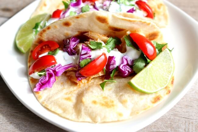 Alaska Cod Fish Tacos with Garlic Lime Sour Cream (slow cooker, instant pot or oven)--well seasoned flaky white fish is served wrapped up in a freshly cooked tortilla and topped with purple cabbage, tomatoes and the best sour cream of your life. A fresh, healthy and easy family friendly recipe that is perfect for any day of the week! Plus you can choose how you want to prepare it--oven, slow cooker or instant pot!