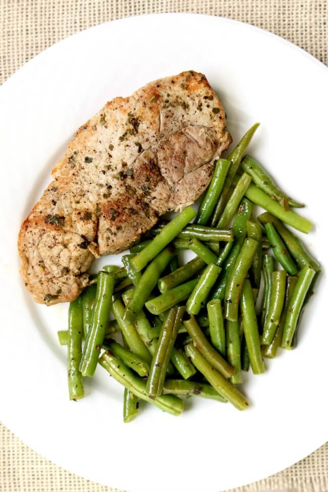 Slow Cooker Garlic Herb Pork Chops and Green Beans--slow cooked pork chops and green beans are full of rich buttery herb flavors. Serve as is for a low-carb meal or serve with your favorite starch (potatoes, rice or noodles).