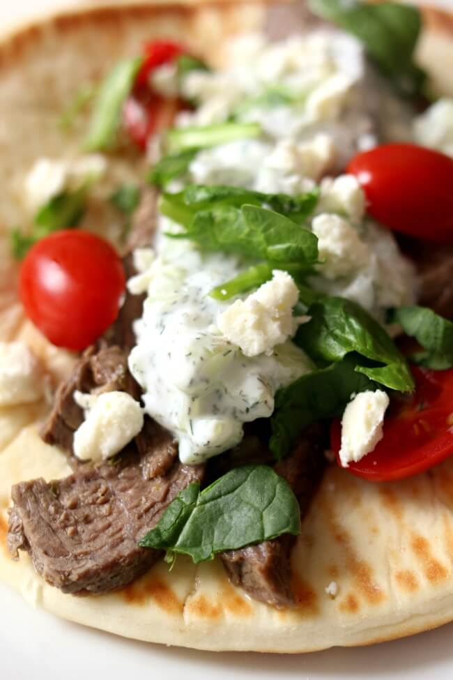 Instant Pot Steak Gyros--tender, seasoned pieces of steak rolled up in a soft pita with tzatziki sauce, tomatoes, onions, lettuce and feta cheese. An easy meal that tastes amazing any night of the week!