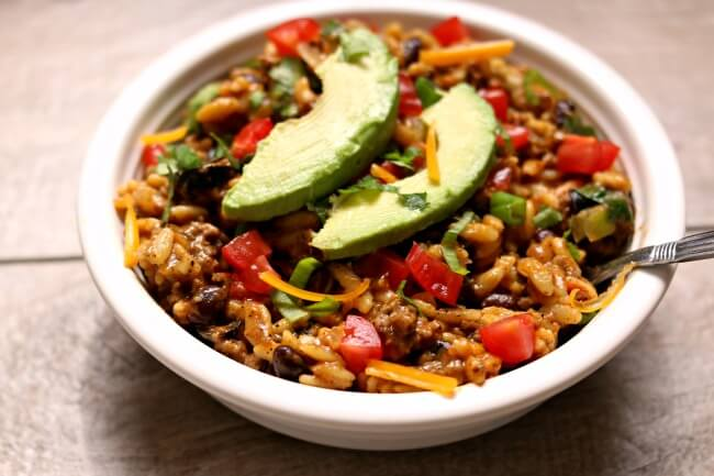 Instant Pot Cheesy Taco Orzo--an easy one pot meal that has a lot of Mexican flare. Orzo pasta is cooked quickly in your pressure cooker along with ground beef, taco sauce and black beans. Fresh ingredients like diced tomatoes, green onions, cilantro and shredded cheddar are stirred in later to create a family friendly and flavorfulmeal.
