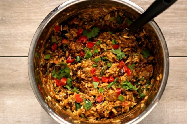 Instant Pot Cheesy Taco Orzo--an easy one pot meal that has a lot of Mexican flare. Orzo pasta is cooked quickly in your pressure cooker along with ground beef, taco sauce and black beans. Fresh ingredients like diced tomatoes, green onions, cilantro and shredded cheddar are stirred in later to create a family friendly and flavorful meal.