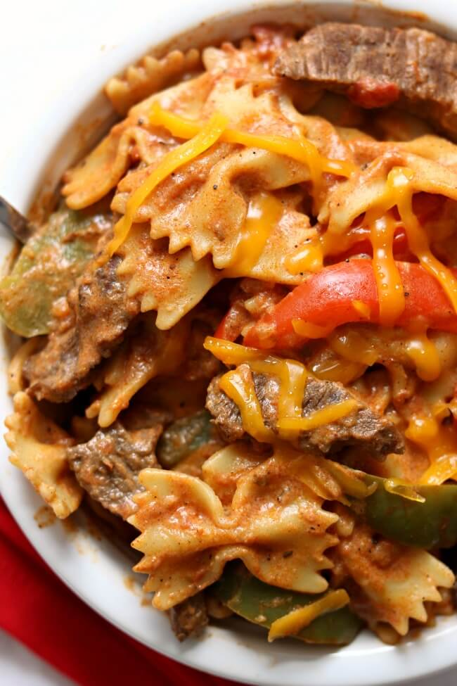 Instant Pot Steak Fajita Pasta--all the delicious flavors of fajitas in a pasta dish! Steak is cooked with fajita seasonings, pasta and tender, but not overcooked, bell peppers. Sour cream is stirred in to add a creamy element to the pasta dish and ties everything together. Make this recipe is just minutes with your electric pressure cooker.