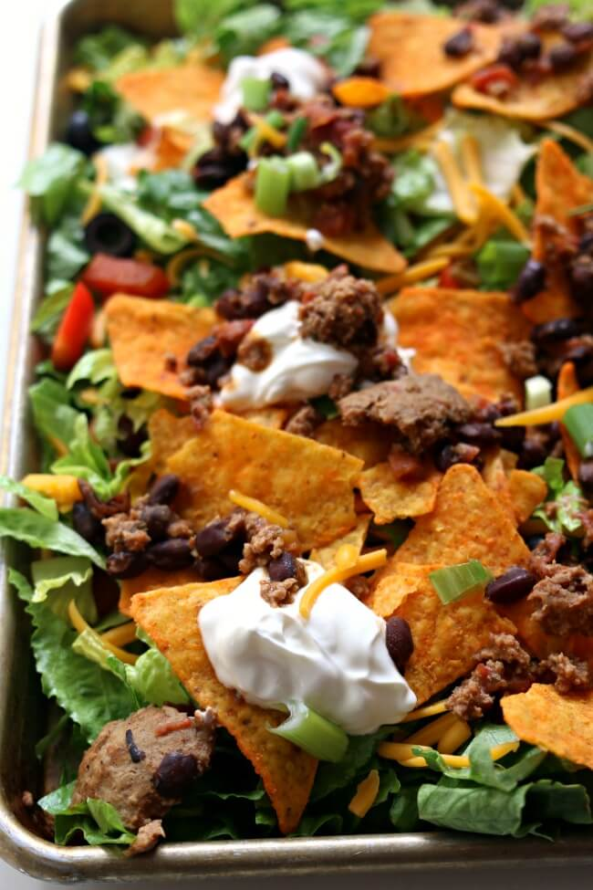 Instant Pot Forgot to Defrost Doritos Taco Salad--this fun spin on taco salad is made quickly even with frozen meat straight from your freezer. Use your Instant Pot to cook the seasoned meat quickly. Layer everything on a sheet pan and dig in for a delicious, healthy, family-friendly dinner.