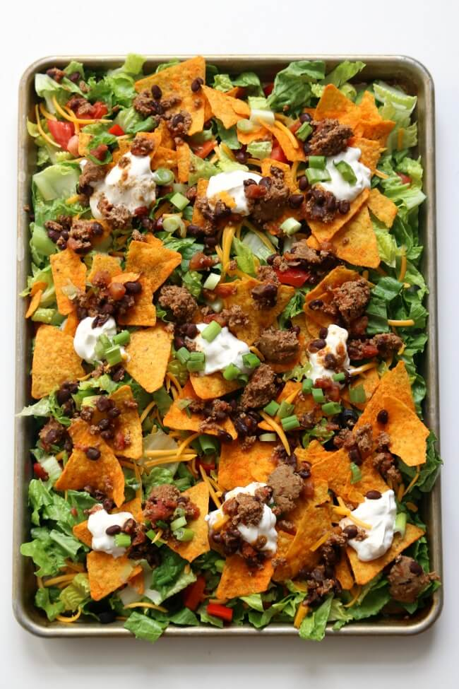 Slow Cooker Forgot to Defrost Doritos Taco Salad--this fun spin on taco salad is made even with frozen meat straight from your freezer. Use your slow cooker to cook the seasoned meat while you're at work. Layer everything on a sheet pan and dig in for a delicious, healthy, family-friendly dinner.