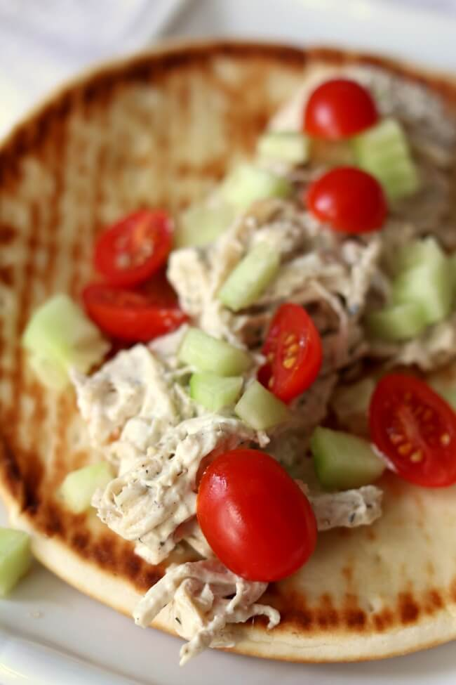 Slow Cooker Creamy Greek Chicken Pitas--a very easy recipe with just a handful of ingredients that tastes absolutely amazing! Cream cheese is stirred into shredded chicken with Greek seasonings and lemon juice and then served on pita bread and topped with tomatoes and cucumbers.  A simple family friendly meal that everyone will love.