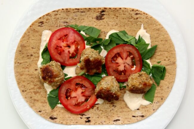 Slow Cooker Lemon Chicken Meatball Wraps with Spicy Garlic Sauce--flavorful lemon chicken meatballs are served rolled up in flatbread with lettuce, tomato and a sour cream/mayo mixture with lots of garlic and sriracha flavor. A perfect summer meal!