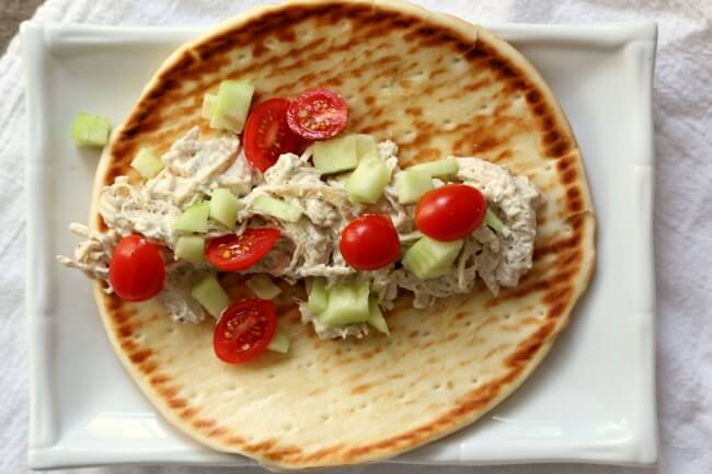 Instant Pot Creamy Greek Chicken Pitas--a very fast and easy recipe with just a handful of ingredients that tastes absolutely amazing! Cream cheese is stirred into shredded chicken with Greek seasonings and lemon juice and then served on pita bread and topped with tomatoes and cucumbers.  A simple family friendly meal that everyone will love.
