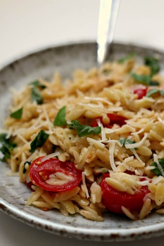 Instant Pot Tomato Basil Parmesan Orzo--orzo pasta is tossed with fresh basil, garlic, halved cherry tomatoes and parmesan cheese for a perfect side dish or meatless meal.