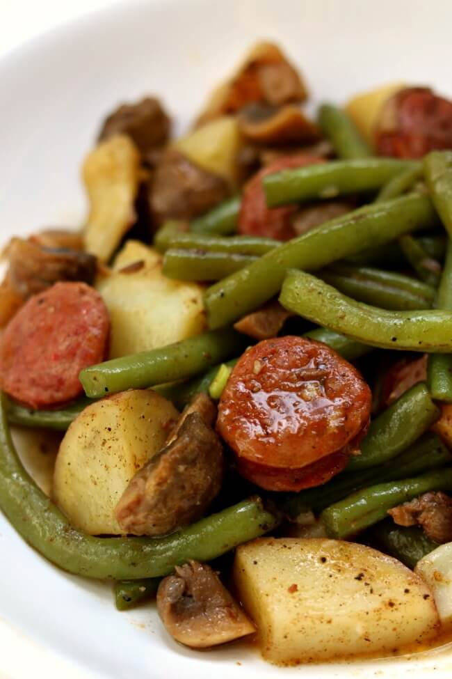 Slow Cooker Cajun Sausage, Potatoes and Green Beans--an easy one pot meal of cajun-style andouille sausage, quartered red potatoes, fresh green beans and sliced mushrooms. Drizzle the buttery broth over the potatoes for maximum flavor