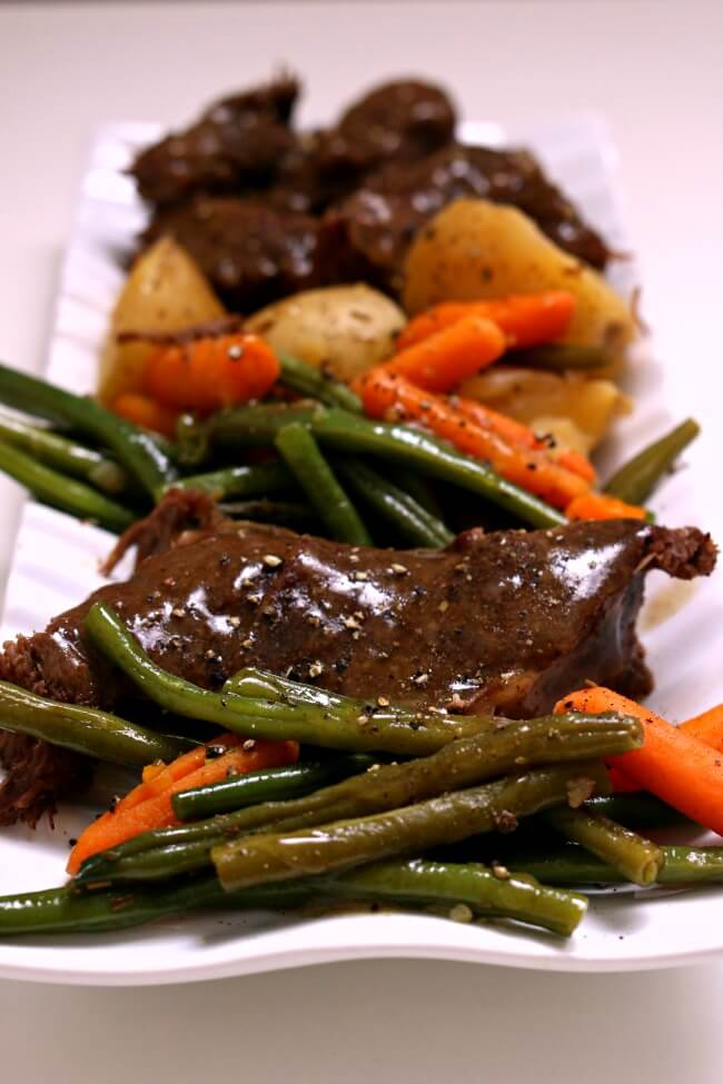 Slow Cooker Grandma's Sunday Roast--get fall apart roast paired with potatoes, carrots, green beans and gravy made easy in your slow cooker. A perfect Sunday dinner just like Grandma used to make.
