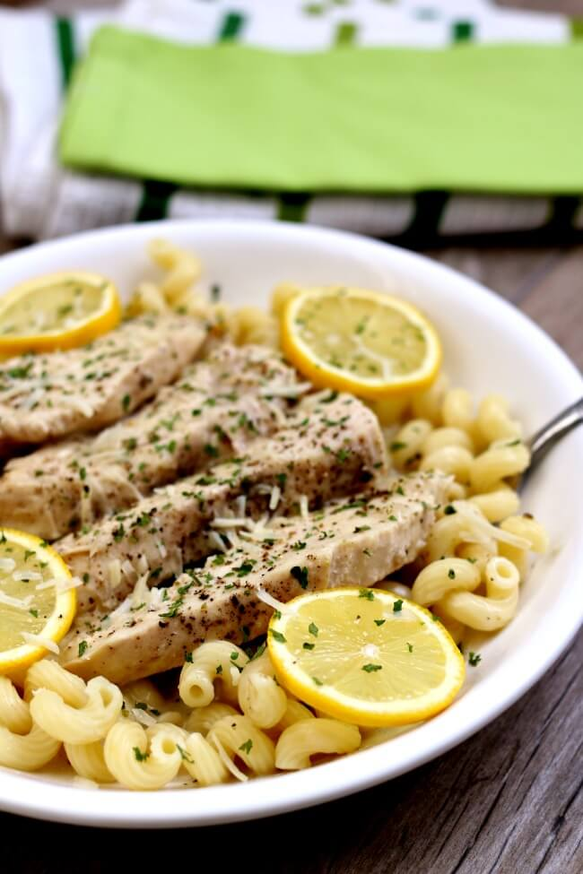Slow Cooker Creamy Lemon Parmesan Chicken--tender bites of chicken enveloped in a creamy parmesan and lemon sauce. Serve the chicken and sauce with pasta, rice or even zoodles.