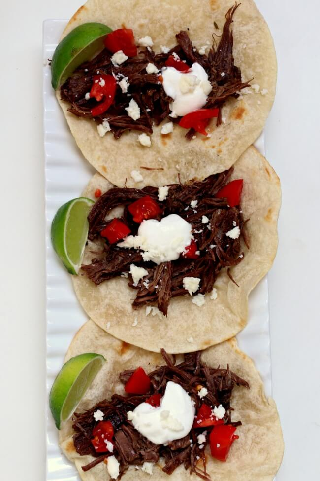 Slow Cooker Shredded Beef Street Tacos--small tortillas are piled with tender shredded seasoned beef, sour cream, tomatoes, cotija cheese and a squeeze of lime. The beef is cooked low and slow and becomes super tender in a over many hours.