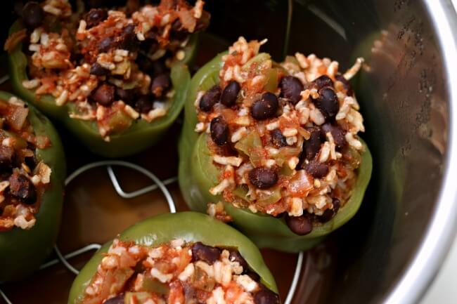 Instant Pot/Slow Cooker Mexican Stuffed Peppers--bell peppers are stuffed with brown rice, black beans and salsa and cooked perfectly in your electric pressure cooker or your crockpot. You can make them vegetarian or with meat, it's up to you. Top with a dollop of sour cream and enjoy this healthy weeknight dinner.