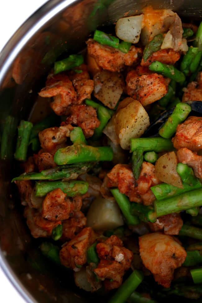 Instant Pot Chicken Asparagus Potato Dinner--moist bites of chicken, cubed potatoes and crisp bites of asparagus are tossed with a seasoning blend of smoked paprika, garlic powder and more to create a well seasoned one pot dinner. Use the Instant Pot to make this dinner quickly.