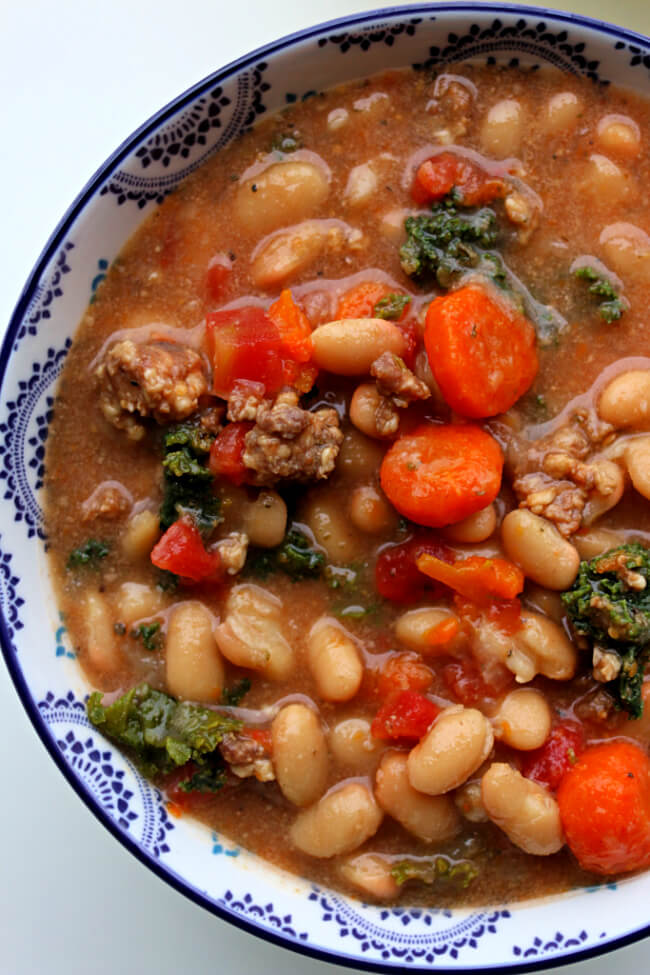 Slow Cooker Tuscan Sausage White Bean Soup--dried white beans (or canned) are slow cooked and make an amazing soup with Italian sausage, carrots, tomatoes, kale and parmesan cheese. The flavor is unbelievably good! This soup is naturally gluten free.