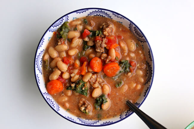 Instant Pot Tuscan Sausage White Bean Soup--dried white beans are quickly pressure cooked and make an amazing soup with Italian sausage, carrots, tomatoes, kale and parmesan cheese. The flavor is unbelievably good! This soup is naturally gluten free.