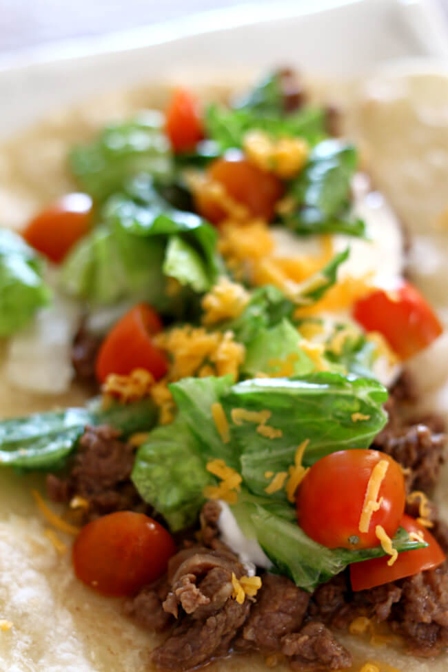 Slow Cooker Carne Asada Street Tacos--an easy way to make carne asada! Throw everything into the crockpot and walk away. Serve the meat over small fresh soft flour tortillas and top with your favorite taco toppings.