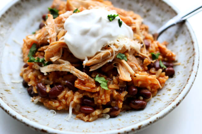 Instant Pot Chicken Rice Bowls--An easy dump and go recipe with chicken, rice (of your choice), enchilada sauce, black beans and spices. This is a perfect dinner for a busy weeknight or a good option to pack in individual containers for lunches during the week.