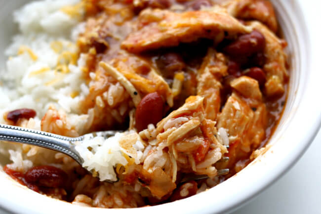 Slow Cooker Southwest Shredded Chicken Bowls--a stew that is bursting with flavor but not too spicy. It has tender shredded chicken, pinto beans, fire roasted tomatoes, green chiles and taco seasoning. Serve this stew over rice or plain for an easy weeknight dinner.
