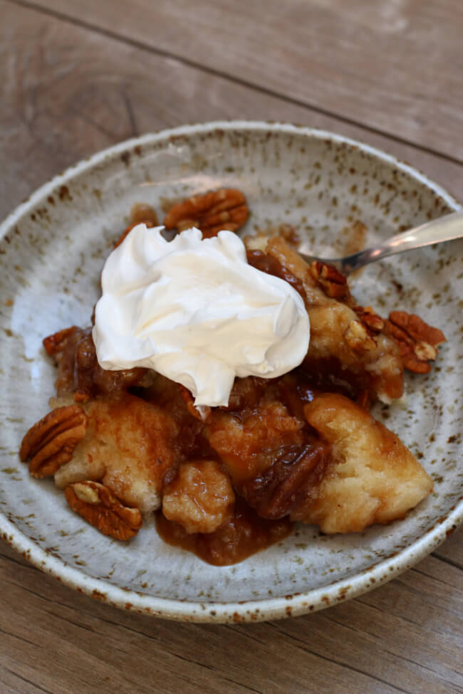 Slow Cooker Praline Pecan Cobber--a gooey, caramelly praline pecan cobbler dessert that will blow your socks off. With a scoop of vanilla ice cream or whipped cream it tastes like heaven in your mouth.