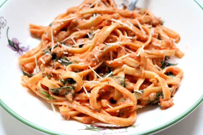 Instant Pot Creamy Tomato Parmesan Fettuccine--a big bowl of noodles with a creamy tomato sauce, spinach, Italian sausage and parmesan cheese.
