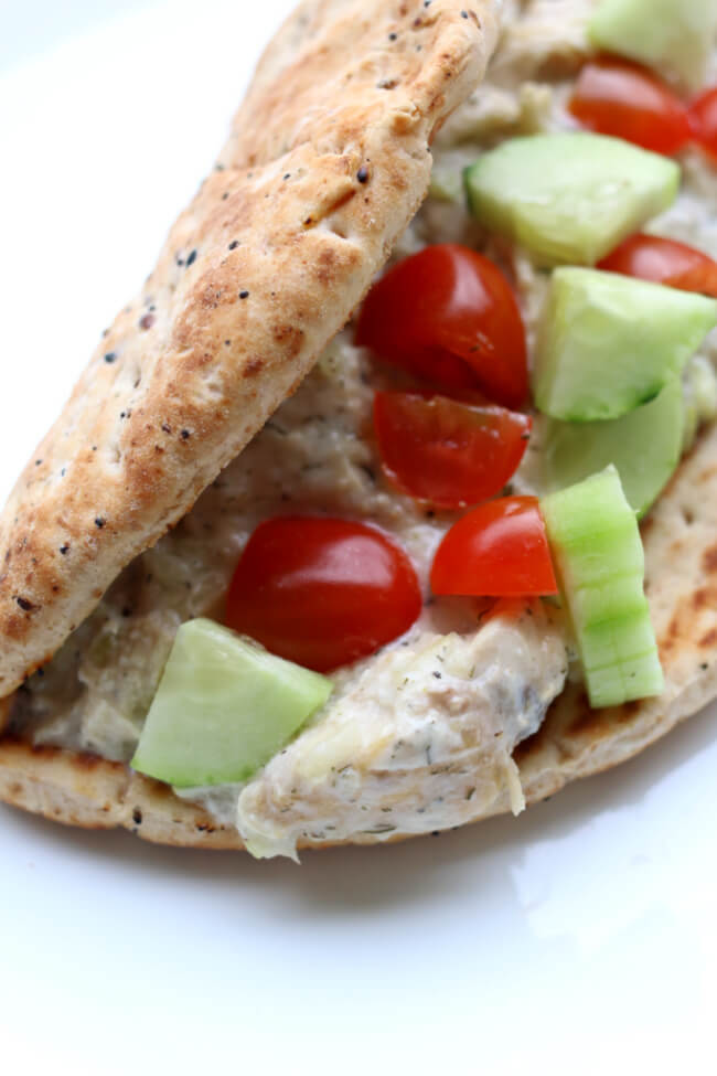 Instant Pot Creamy Dill Chicken--chicken with garlic, lemon pepper, dill, and lemon juice encoated in creamy yogurt and then wrapped in a warm pita with diced cucumbers and cherry tomatoes. A perfect summer meal!