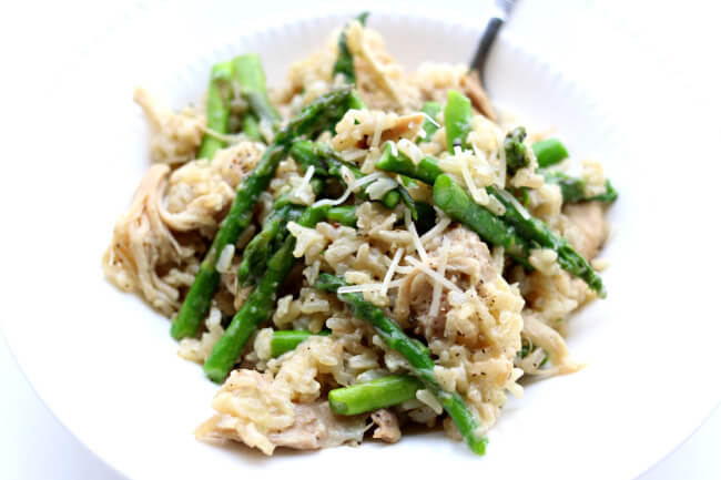 Slow Cooker Garlic Rice and Chicken--brown rice is cooked with fresh garlic and tender bites of chicken. Parmesan cheese and asparagus (or broccoli) are stirred in to make a perfect one pot meal.