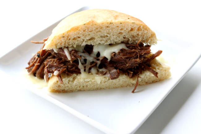 Slow Cooker Garlic Beef Sandwiches--fork tender roast beef that is flavored with garlic and other filipino adobo flavors. Perfect to serve on rolls or over rice for a quick and easy dinner that can feed a crowd.